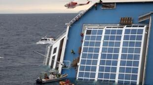 Equipe de resgate escala o convés do navio Costa Concordia nesta segunda-feira.