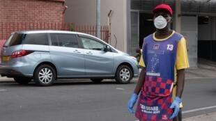 Un voiturier porte des gants et un masque alors qu'il travaille dans les rues de Windhoek, le 16 mars 2020, au début de l'épidémie de Covid-19.