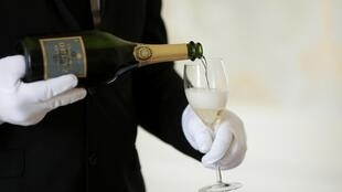 n employee serves a glass of Champagne during the traditional wine harvest at the Champagne house Deutz in Ay, France.