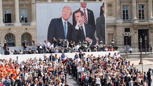 Telão na praça da Concórdia, em Paris, exibe imagens da tribuna de honra onde Emmanuel Macron e Donald Trump assistem ao desfile militar de 14 de julho na avenida Chaps Elysée.