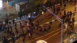 An image grab taken from a handout video released by Iran's Mehr News agency reportedly shows a group of men pulling at a fence in a street in Tehran on December 30, 2017.