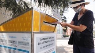 Une électrice américaine place son bulletin pour l'élection présidentielle du 3 novembre dans une boîte prévue pour le vote par correspondance, à Los Angeles, le 5 octobre 2020.