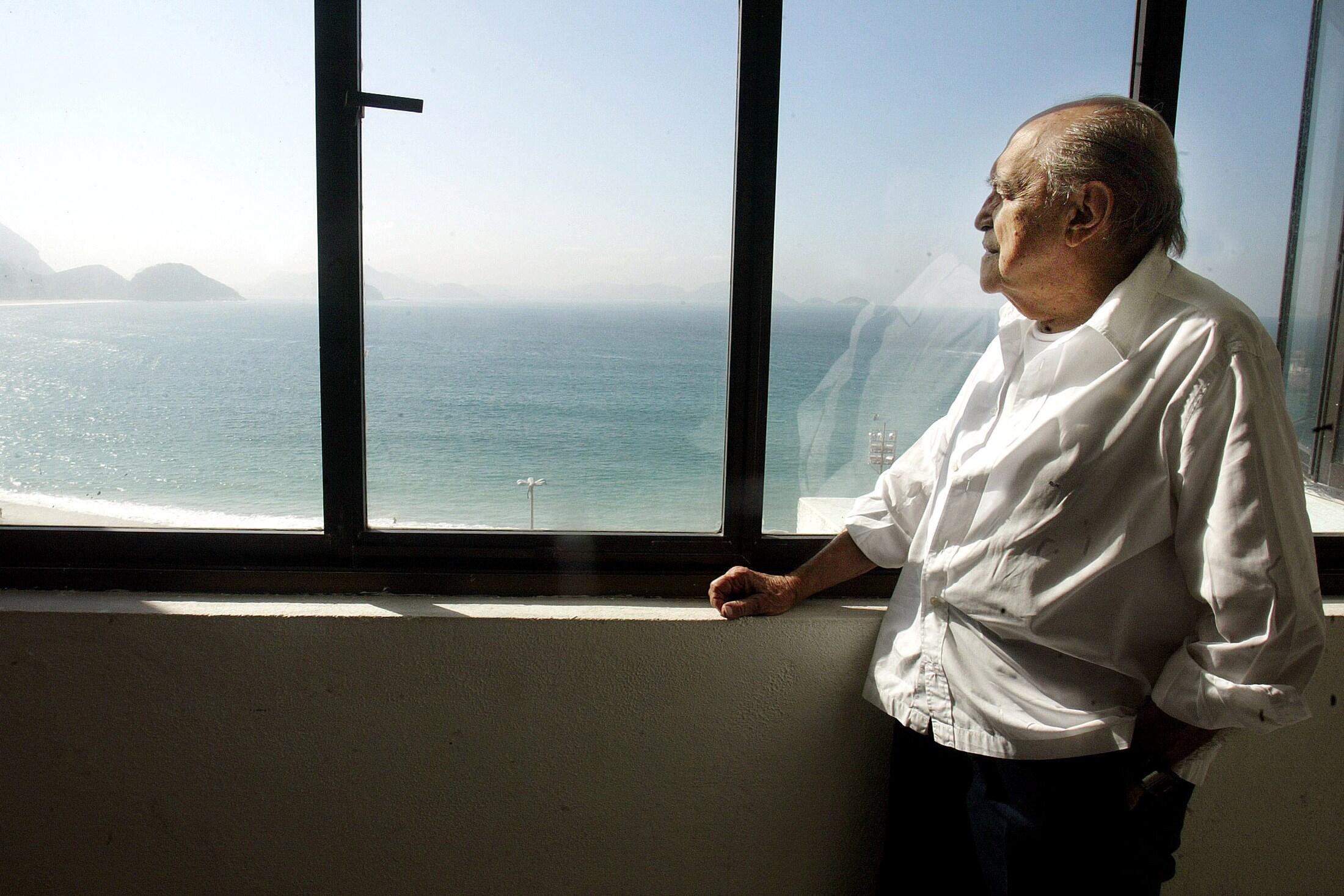 Oscar Niemeyer mirando la playa de Copacabana desde su oficina, en 2003.