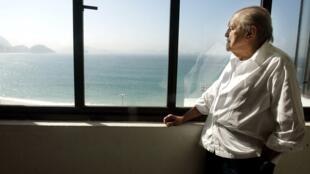 Oscar Niemeyer regardant la plage de Copacabana, depuis son bureau, le 16 juin 2003.