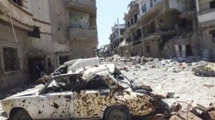 Carro destruído em meio a escombros em Homs. Foto de 28 de abril