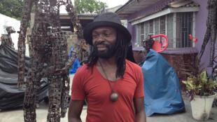 Freddy Tsimba devant l'une de ses sculptures faite à base de cuillère et de couverts récupérés.