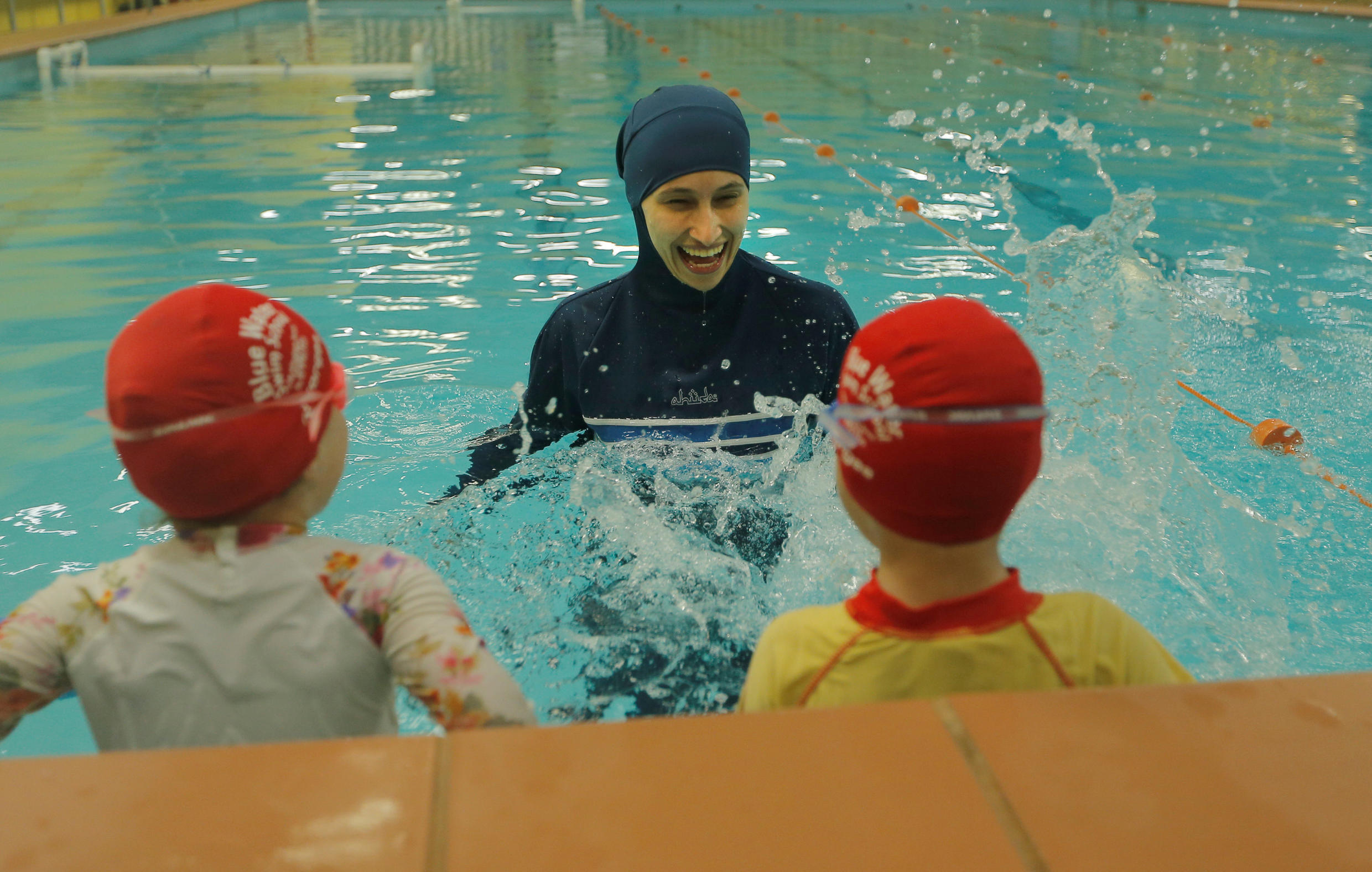 Australian muslim swimming instructor Fadila Chafic wears a burkini during a swimming lesson with her children Taaleen (L) and Ibrahim in Sydney