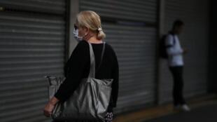 Une Brésilienne passe devant un centre commercial fermé à cause de l'épidémie de coronavirus, à Sao Paulo, le 19 mars 2020.