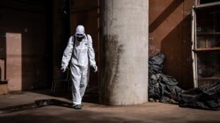 Un employé désinfecte le marché Rood Woko de Ouagadougou pour lutter contre la propagation du coronavirus, le 31 mars 2020.