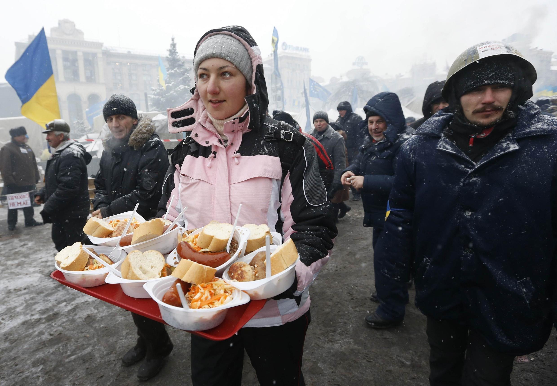 Des bénévoles distribuent de la nourriture et des boissons chaudes aux manifestants de la place de l'Indépendance à Kiev, le 11 décembre 2013.