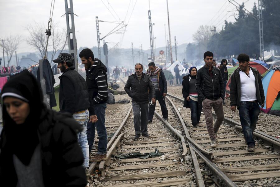 Des réfugiés et des migrants marchent le long d'une voie ferrée dans un camp de fortune à la frontière Greco-Macédonienn, en mars 2016.