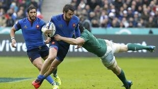 France's Maxime Medard (centre) is tackled by Ireland's Eoin Reddan during their Six Nations tournament match at Stade de France near Paris on Saturday.