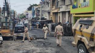 La police patrouille dans le quartier de Kaval Byrasandra, à Bangolore, où plusieurs véhicules et bâtiments ont été incendiés.