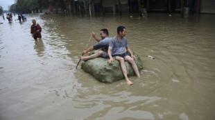 Pessoas atravessam ruas inundadas na província de Sichuan em bote improvisado.