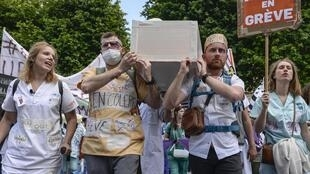 People take part in a demonstration in Paris on 6 June, 2019 gathering public hospital emergency services members called by the Inter-Emergency collective and several unions to demand better salaries and more staff.