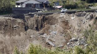 一辆轿车悬在地震坍塌地面边缘