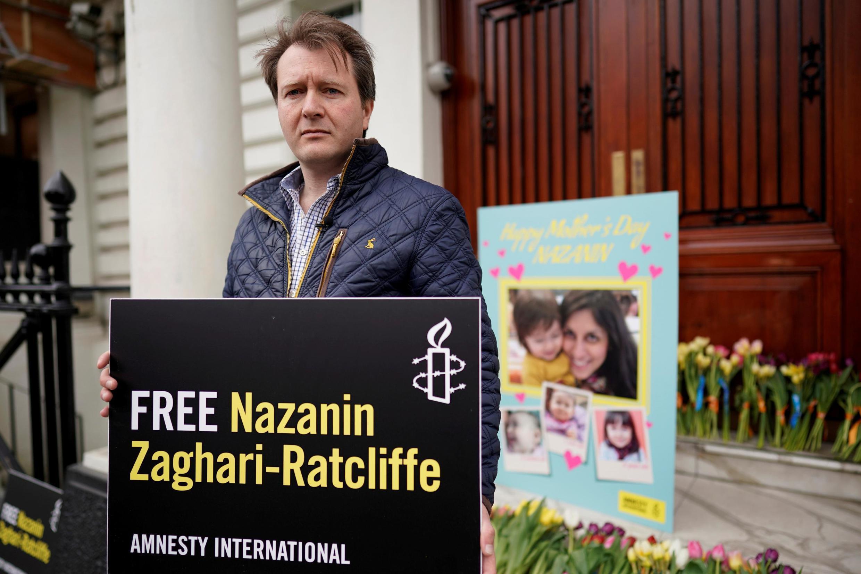 """Richard Ratcliffe, chồng của bà Nazanin Zaghari-Ratcliffe, đến đặt thiệp, ảnh vợ con và hoa nhân """"Ngày các bà Mẹ"""" trước sứ quán Iran tại Luân Đôn, ngày 31/03 2019."""