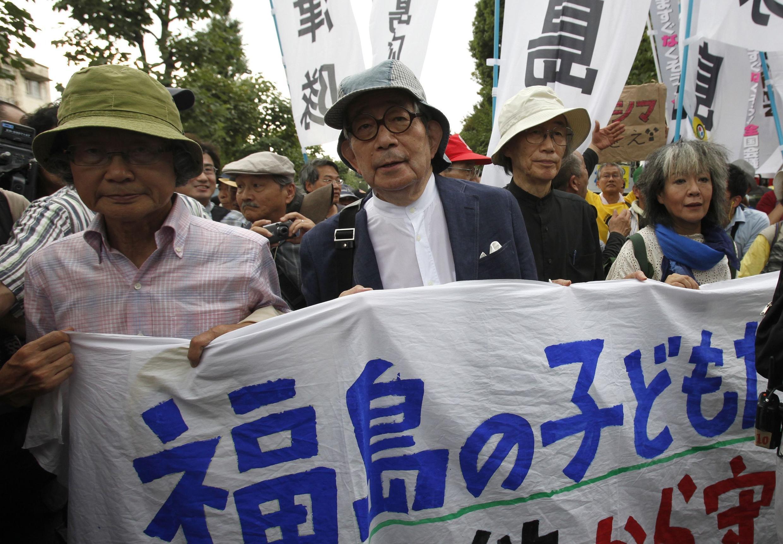 """Biểu tình tại Tokyo ngày 19/9/2011 nhằm thu thập 10 triệu chữ ký phản đối hạt nhân. Khẩu hiệu ghi dòng chữ """"Bảo vệ trẻ em Fukushima khỏi nhiễm xạ"""". Giải Nobel văn học Kenzaburo Oe (hai trái sang). REUTERS/Yuriko Nakao"""