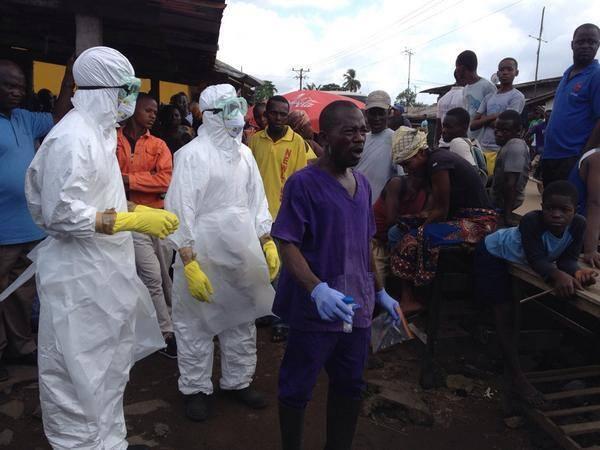 Les équipes de la Croix-Rouge se préparent à emporter le corps d'une victime décédée d'Ebola. Il va falloir brûler le corps.
