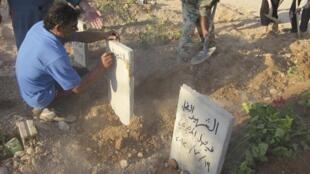 Một người đang viết tên lên bia mộ một nạn nhân bị quân chính phủ Syria sát hại, ngày 19/07/2012.