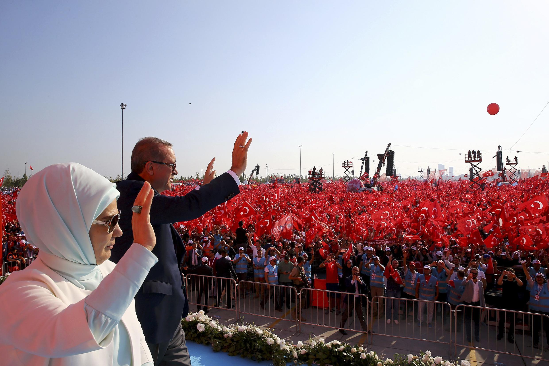 Presidente Erdogan e sua esposa, Emine Gulbaran, acenam para os milhares de manifestantes que participaram de ato em Istambul.