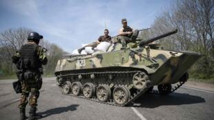 Soldados ucranianos montam guarda fora da cidade de Slaviansk neste domingo (27); o exército ucraniano tenta isolar esse reduto dos separatistas pró-russos.