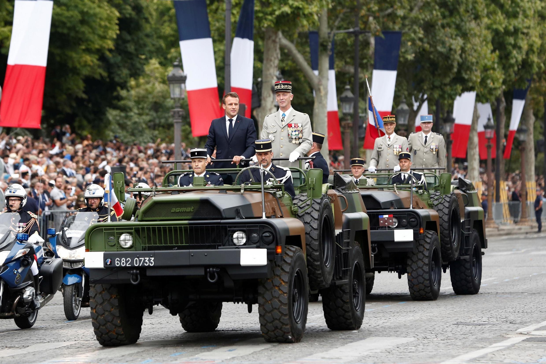 Президент Эмманюэль Макрон в сопровождении главы генштаба армии Франсуа Лекуантра проводит смотр войск на Елисейских полях, 14 июля 2019 года