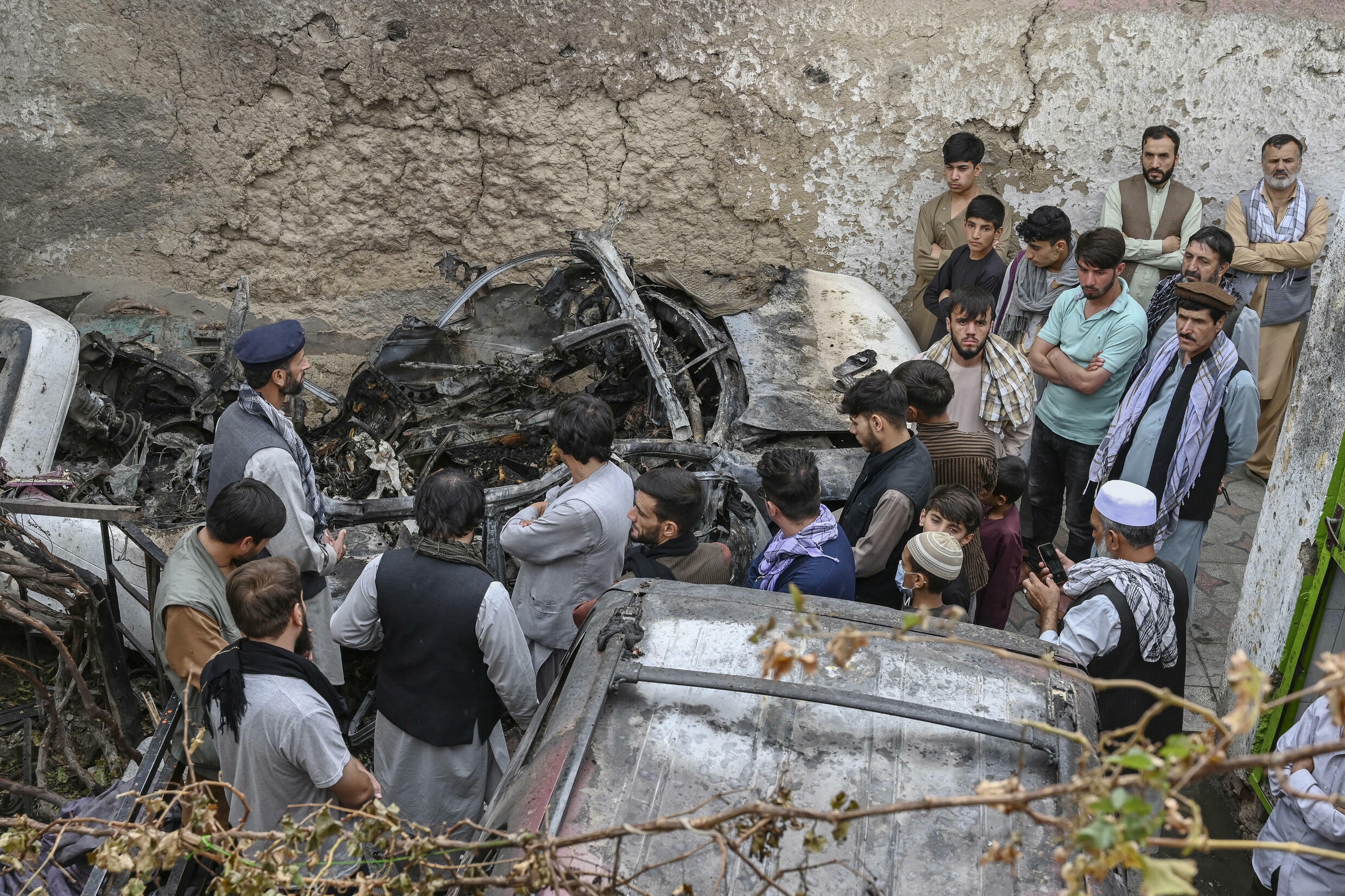 Afghan relatives gather on August 30, 2021 next to a damaged vehicle after a US drone strike that has come under scrutiny