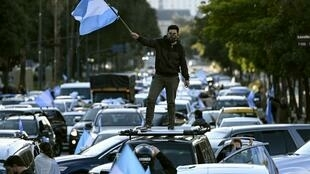 A man waves the Argentine flag during a protest against President Alberto Fernandez's health policies during the coronavirus pandemic in Buenos Aires on July 9, 2020