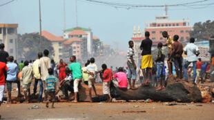 Des manifestants se tiennent debout sur des barricades, dans une banlieue de Conakry, alors que des violences éclatent dans la capitale, le 14 avril 2015.