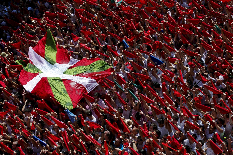 Foliões com lenços vermelhos e bandeiras bascas, no início da Festa de San Fermin, em Pamplona.