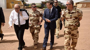FILE PHOTO: French President Emmanuel Macron (C) and French Foreign Affairs Minister Jean-Yves Le Drian (L) visit the troops of France's Barkhane operation in Africa's Sahel region in Gao, northern Mali, 19 May 2017