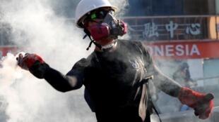 Un manifestant renvoie une bombe lacrymogène sur la police lors d'une manifestation en faveur de réformes démocratiques à Hong Kong, le 5 août 2019.
