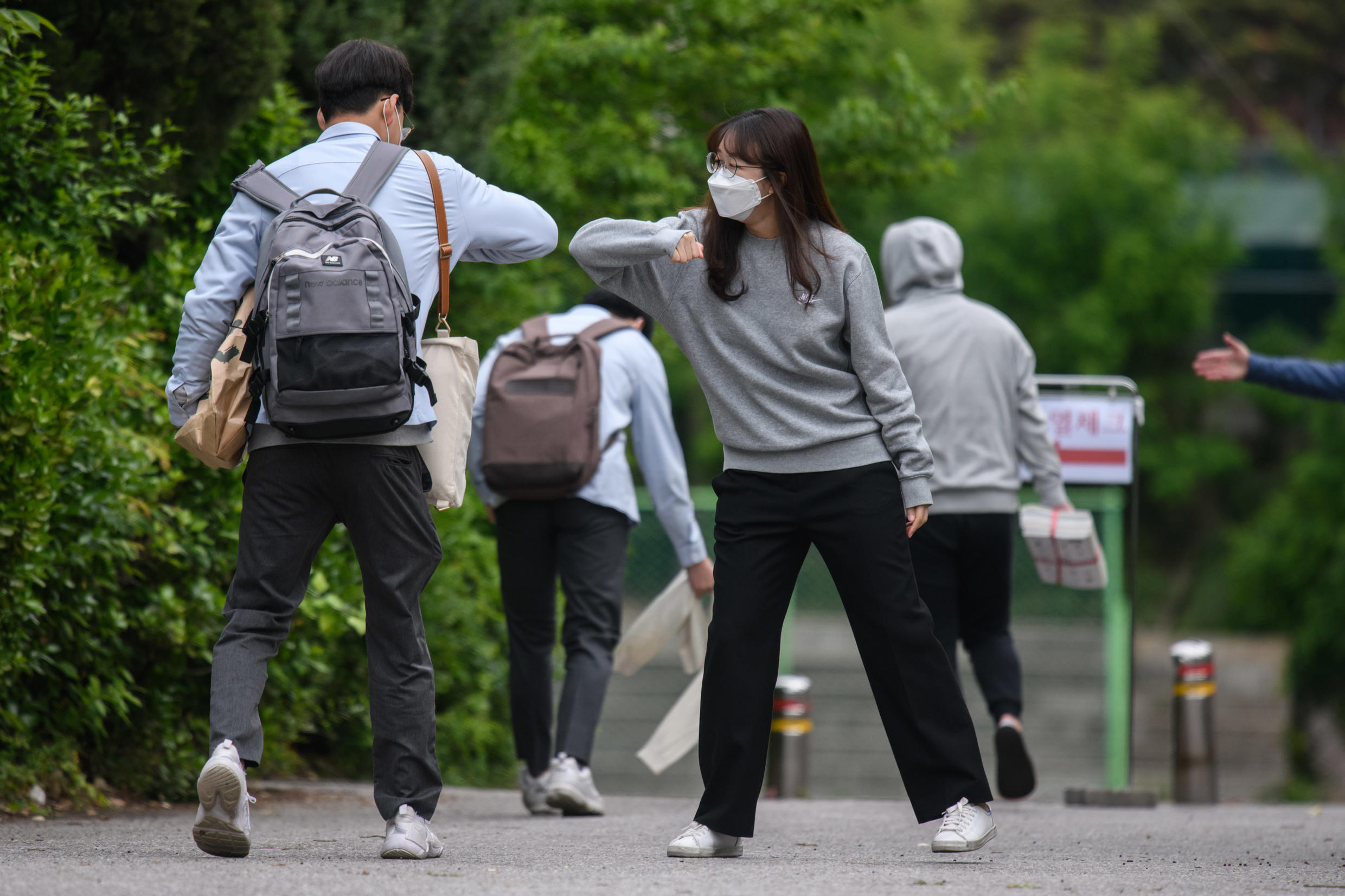 A staff member greeted students with an elbow bump as they returned to Kyungbock High School in Seoul after being closed for more than two-months because of coronavirus