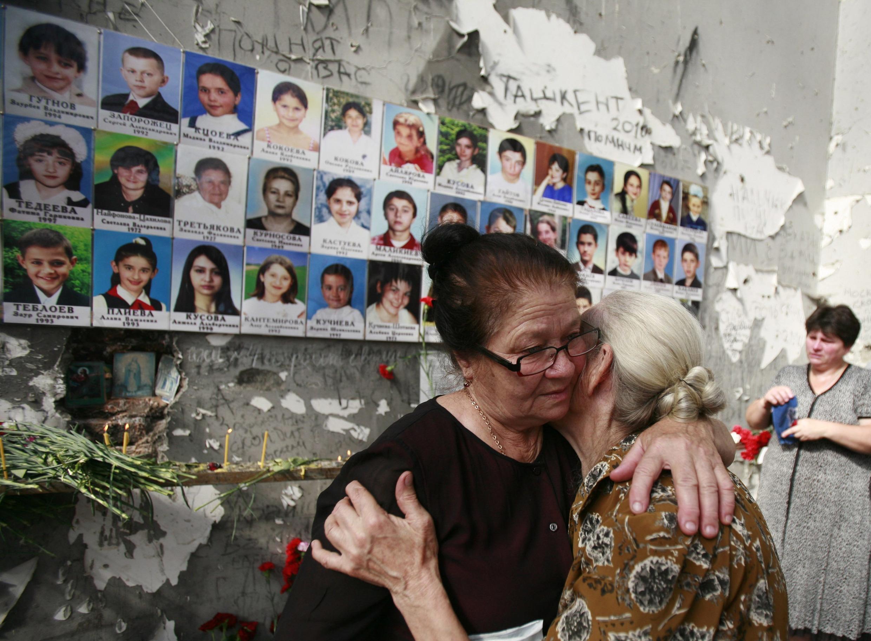 Pessoas choram durante cerimônia em homenagem às vítimas da escola de Beslan, na Rússia