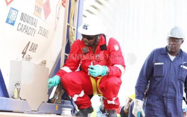 Tullow Oil workers inspect a consignment of crude oil from its Turkana oil fields at the Kenya Petroleum Refinery Ltd in Mombasa