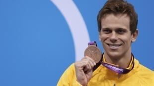 O nadador César Cielo mostra sua medalha de bronze após conseguir o terceiro lugar na prova de 50 metros livre, nesta sexta-feira, em Londres.