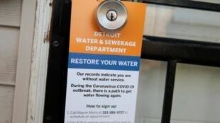 Un accroche-porte qui explique les démarches à suivre pour que l'eau soit rétablie au domicile, dans un quartier pauvre de Detroit dans le Michigan.