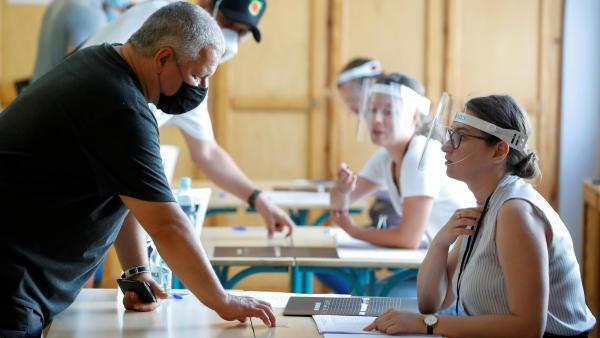 Respect scrupuleux des règles sanitaires liées à la pandémie du Covid-19, dans un bureau de vote de Varsovie, dimanche 28 juin.