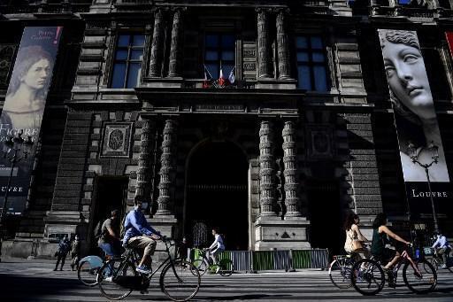 Cyclistes devant le musée du Louvre, à Paris.