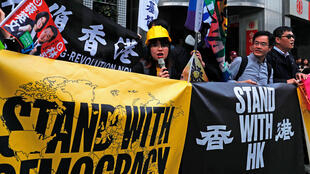 Des manifestants antigouvernementaux de Hong Kong tiennent une bannière pour demander le soutien de la présidente taïwanaise Tsai Ing-wen lors d'un événement de campagne à Taipei, le 10 janvier 2020.