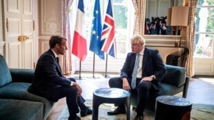 O presidente francês, Emmanuel Macron, e o primeiro-ministro britânico, Boris Johnson, conversam durante reunião no Palácio do Eliseu, em Paris.