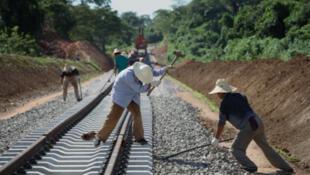 Des travailleurs chinois fixent les rails du chemin de fer de Dondo, en Angola.