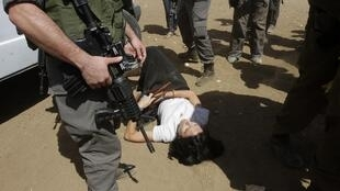 French diplomat Marion Fesneau-Castaing at the feet of Israeli troops
