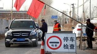 """2021年1月12日,在与中国河北省交界处的北京郊区,""""志愿者们""""在盘查进入北京的汽车。"""