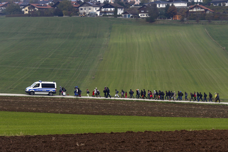 Inmigrantes escoltados por la policía alemana hasta un centro de registro después de cruzar la frontera austriaco-alemana cerca de Passau, el 20 de octubre de 2015.