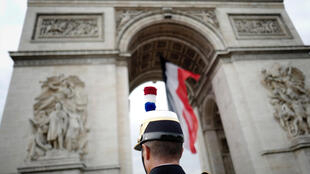 French soldier stands near the Arc de Triomphe in Paris.