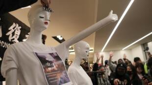 Des manifestants de Hong Kong habillent des mannequins de slogans alors qu'ils défilent dans le centre commercial Harbor City à Hong Kong, en Chine, le 21 décembre 2019.