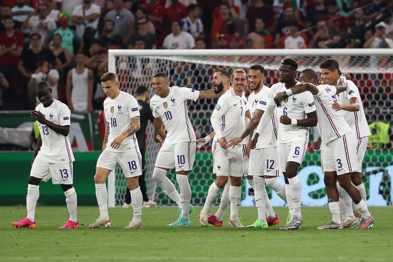 La joie de l'attaquant français Karim Benzema (c), félicité par ses coéquipiers, après avoir marqué sur pénalty face au Portugal, lors de la 3e journée du groupe F à l'Euro 2020, le 23 juin 2021 à Budapest