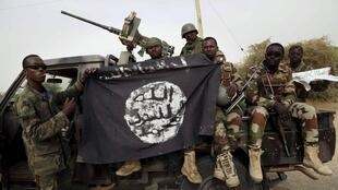 Des soldats nigériens brandissent un drapeau de Boko Haram, récupéré lors de la prise de Damasak, le 18 mars 2015.